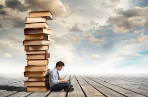 Column of books and young man with laptop